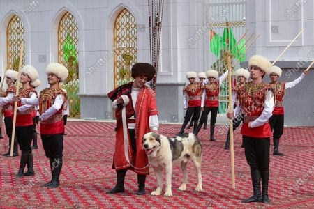 Man dressed in a national costume, center, pets his border guard shepherd dog Alabai during Dog Day celebration in Ashgabat, Turkmenistan, . The Central Asian nation of Turkmenistan has celebrated its new state holiday honoring the native Alabay dog breed. President Gurbanguly Berdymukhamedov established the holiday to be observed on the same day that Turkmenistan lauds its Akhla-Teke horse, a breed known for its speed and endurance