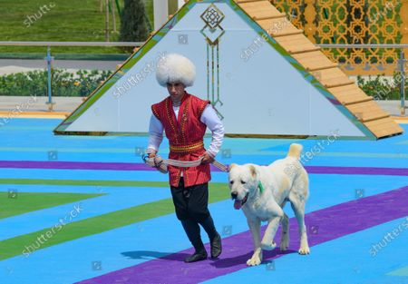 Man dressed in a national costume runs with his border guard shepherd dog Alabai during Dog Day celebration in Ashgabat, Turkmenistan, . The Central Asian nation of Turkmenistan has celebrated its new state holiday honoring the native Alabay dog breed. President Gurbanguly Berdymukhamedov established the holiday to be observed on the same day that Turkmenistan lauds its Akhla-Teke horse, a breed known for its speed and endurance