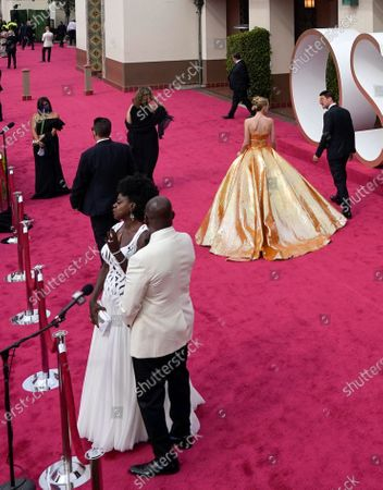 Viola Davis, from left, and Julius Tennon are interviewed while Carey Mulligan walks the red carpet at the Oscars
