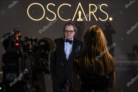 Gary Oldman is interviewed upon arrival at a screening of the Oscars