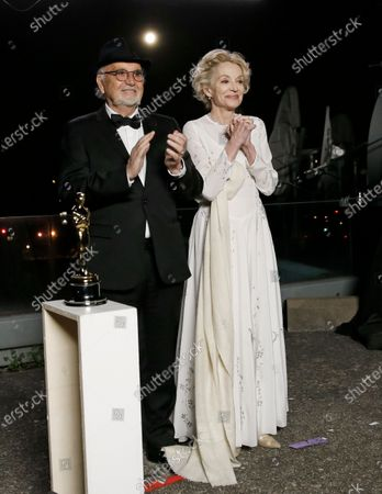 Jean-Louis Livi and Caroline Silhol pose for a photo during a screening of the Oscars on Monday April 26, 2021 in Paris, France.