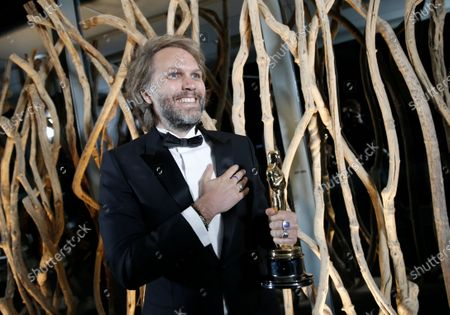 Florian Zeller smiles as he holds his Oscars statuette after winning the Best Adapted Screenplay for the 'The Father' at a screening of the Oscars on in Paris, France