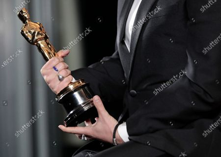 Florian Zeller holds his Oscars statuette after winning the Best Adapted Screenplay for the 'The Father' at a screening of the Oscars on in Paris, France