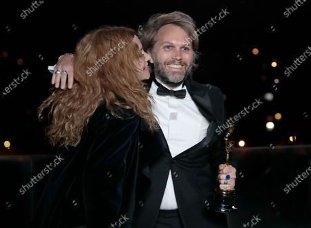 Florian Zeller embraces Marine Delterme as he holds his Oscars statuette after winning the Best Adapted Screenplay for the 'The Father' at a screening of the Oscars on in Paris, France