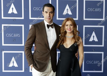 Sacha Baron Cohen and Isla Fisher pose for a photo during a screening of the Oscars