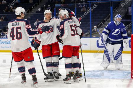 Stock Photo of Columbus Blue Jackets' Eric Robinson (50) celebrates his goal with Dean Kukan (46) and Gavin Bayreuthe as Tampa Bay Lightning goaltender Andrei Vasilevskiy reacts during the third period of an NHL hockey game, in Tampa, Fla. The Lightning won 4-3