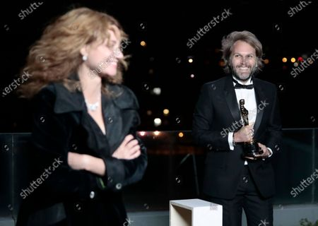 Stock Photo of Florian Zeller smiles toward Marine Delterme as he holds his Oscars statuette after winning the Best Adapted Screenplay for the 'The Father' at a screening of the Oscars