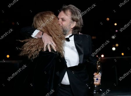 Florian Zeller embraces Marine Delterme as he holds his Oscars statuette after winning the Best Adapted Screenplay for the 'The Father' at a screening of the Oscars