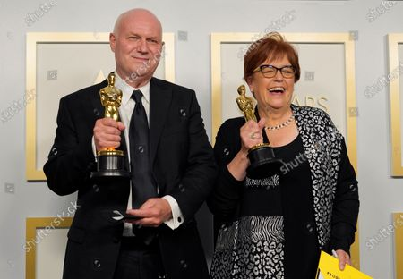 """Donald Graham Burt, left, and Jan Pascale pose with the award for best production design for """"Mank"""" in the press room at the Oscars, at Union Station in Los Angeles"""