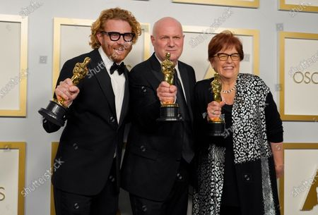 """Erik Messerschmidt, from left, winner of the award for best cinematography for """"Mank"""", Donald Graham Burt and Jan Pascale, winners of the award for best production design for """"Mank"""" pose in the press room at the Oscars, at Union Station in Los Angeles"""