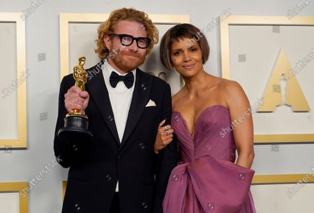 """Erik Messerschmidt, left, winner of the award for best cinematography for """"Mank"""", poses with presenter Halle Berry in the press room at the Oscars, at Union Station in Los Angeles"""