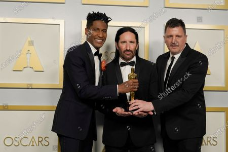 """Jon Batiste, from left, Trent Reznor and Atticus Ross, winners of the award for best original score for """"Soul,"""" pose in the press room at the Oscars, at Union Station in Los Angeles"""