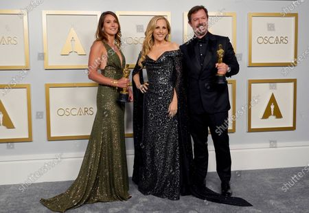 """Pippa Ehrlich, from left, winner of the award for best documentary feature for """"My Octopus Teacher"""", presenter Marlee Matlin and James Reed, winner of the award for best documentary feature for """"My Octopus Teacher"""" pose in the press room at the Oscars, at Union Station in Los Angeles"""