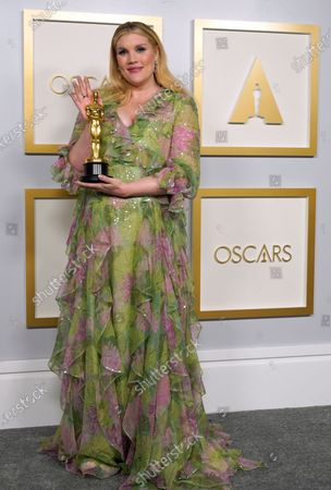 """Emerald Fennell, winner of the award for best original screenplay for """"Promising Young Woman,"""" poses in the press room at the Oscars, at Union Station in Los Angeles"""