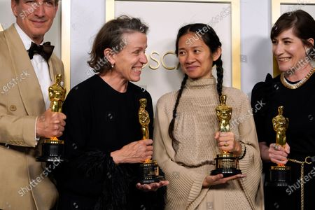 """Producers Peter Spears, from left, Frances McDormand, Chloe Zhao and Mollye Asher, winners of the award for best picture for """"Nomadland,"""" pose in the press room at the Oscars, at Union Station in Los Angeles"""