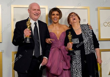 """Donald Graham Burt, left, and Jan Pascale, right, pose in the press room with the award for best production design for """"Mank"""" with Halle Berry, center, at the Oscars, at Union Station in Los Angeles"""