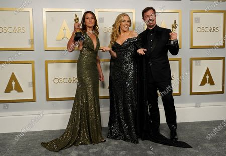 """Pippa Ehrlich, left, and James Reed, right pose in the press room with the award for best documentary feature for """"My Octopus Teacher"""" with Marlee Matlin, center, at the Oscars, at Union Station in Los Angeles"""