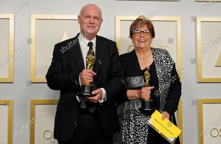 """Donald Graham Burt, left, and Jan Pascale pose in the press room with the award for best production design for """"Mank"""" at the Oscars, at Union Station in Los Angeles"""