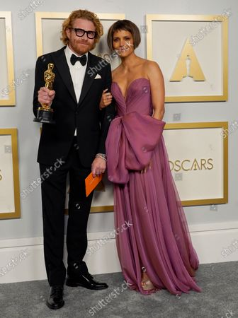 """Erik Messerschmidt, left, winner of the award for best cinematography for """"Mank"""" and Halle Berry, right, pose in the press room at the Oscars, at Union Station in Los Angeles"""