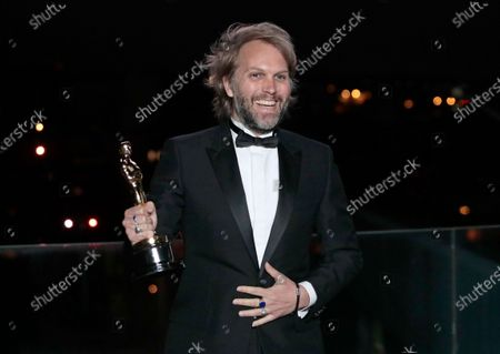 Florian Zeller holds his Oscars statuette after winning the Best Adapted Screenplay for the 'The Father' during the screening for the 93rd annual Academy Awards in Paris, France 26 April 2021. The Oscars are presented for outstanding individual or collective efforts in filmmaking in 24 categories. The Oscars happen two months later than originally planned, due to the impact of the coronavirus COVID-19 pandemic on cinema.