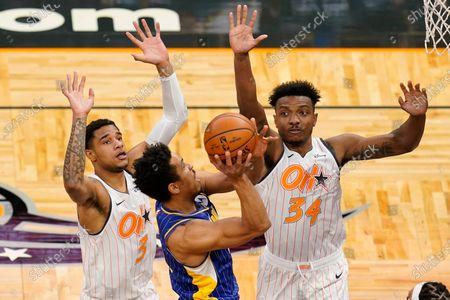 Indiana Pacers guard Malcolm Brogdon, center, makes a shot past Orlando Magic forward Chuma Okeke (3) and center Wendell Carter Jr. (34) during the first half of an NBA basketball game, in Orlando, Fla