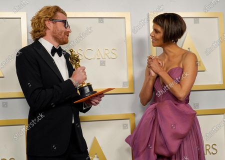 Erik Messerschmidt (L), winner of the award for best cinematography for 'Mank,' poses with Halle Berry (R) in the press room at the 93rd annual Academy Awards ceremony at Union Station in Los Angeles, California, USA, 25 April 2021. The Oscars are presented for outstanding individual or collective efforts in filmmaking in 24 categories. The Oscars happen two months later than originally planned, due to the impact of the coronavirus COVID-19 pandemic on cinema.