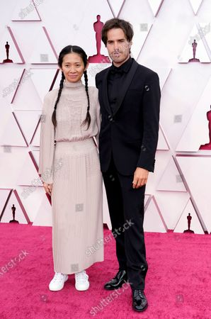 Stock Picture of Chloe Zhao, left, and Joshua James Richards arrive at the Oscars