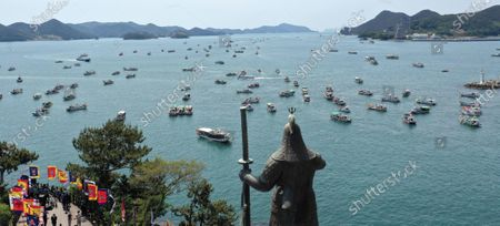 Fishing boats sail in waters off Tongyeong on South Korea's south coast, 26 April 2021, as protesters from the fisheries industry hold a protest rally to slam Japan for its decision to discharge water containing radioactive materials stored at the Fukushima nuclear power plant into the sea. At the front is a statue of Joseon Dynasty (1392-1910) Admiral Yi Sun-sin, who led the Korean Navy against Japanese invaders in the 16th century.