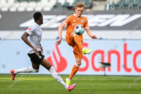 Stock Photo of (210426) - MOENCHENGLADBACH, April 26, 2021 (Xinhua) - Christian Gebauer (R) of Bielefeld controls the ball under the defense from Denis Zakaria of Moenchengladbach during a German Bundesliga match between Borussia Moenchengladbach and Arminia Bielefeld in enchengladbach, Germany, April 25, 2021. (Photo by Ulrich Hufnagel/Xinhua) FOR EDITORIAL USE ONLY. - Ulrich Hufnagel -