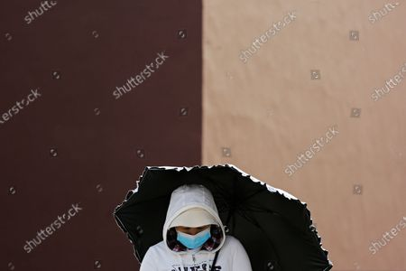 Woman wearing a face mask to help curb the spread of the coronavirus holds an umbrella while walking on a street in Beijing