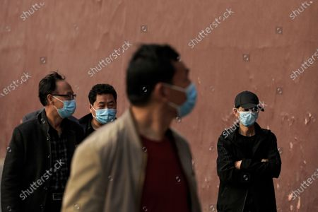 People wearing face masks to help curb the spread of the coronavirus walk on a street in Beijing