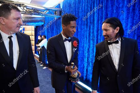 Stock Photo of Atticus Ross, Jon Batiste and Trent Reznor backstage with the Oscar® for Original Score during the live ABC Telecast of The 93rd Oscars® at Union Station in Los Angeles, CA on Sunday, April 25, 2021.