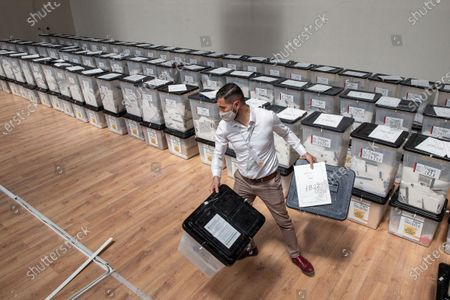 Election official carries ballot boxes for counting at the counting center in capital Tirana, Albania, on . Preliminary results on Monday show the ruling Socialist Party ahead in Albania's parliamentary election. With one-third of the votes counted the left-wing Socialsits of Prime Minister Edi Rama have won 50% of the votes, followed by the main opposition center-right Democratic Party of Lulzim Basha with 39