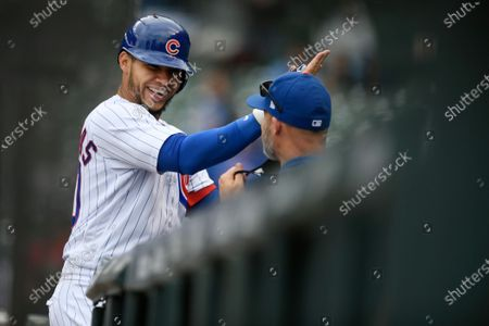 Chicago Cubs' Willson Contreras left, celebrates with manager David Ross right, at the dugout after hitting a three-run home run during the sixth inning of a baseball game against the Milwaukee Brewers, in Chicago. Chicago won 15-2