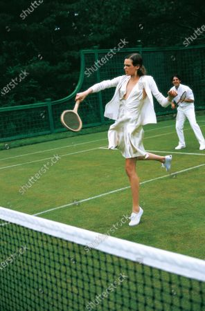 Model Elise Crombez playing tennis in an all white ensemble, including a Prada cashmere cardigan and Donna Karan V-neck dress.