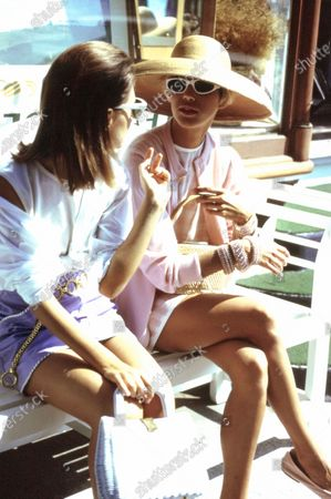 Stock Picture of Two models on a wooden bench in front of a shop: Left: Cashmere shell by N. Peal over a white poplin shirt and leather skirt by Salvatore Ferragamo, gold belt by Paloma Picasso. Bag by Magid. Sunglasses by J.Crew. Right: Cashmere cardigan by Cashmere-Cashmere over a striped short dress by Randolph Duke, with a wide straw hat by Eric Javits. Sunglasses from the Marilyn Monroe Collection for Renaissance Eyewear. Bracelets by Jay Strongwater. Bag by Magid.