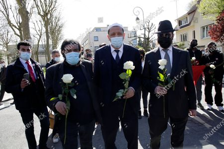 French novelist and philosopher Marek Halter, Imam Hassen Chalghoumi and Rabbi Levi Matusof from Brussels, from left to right, hand white roses to be taken down to the police station where a police official was stabbed death Friday in Rambouillet, south west of Paris, . Police also called for gatherings at police stations around France after the stabbing in Rambouillet, which authorities are investigating as a terrorist attack