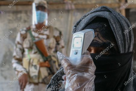 A security personal checks the body temperature of a woman wearing mask  shows before her vote at polling station, during 7th phase of West Bengal assembly elections in Kolkata, India on 26 April, 2021. The 7th phase of West Bengal Assembly Election 2021 ahead Covid-19 Coronavirus pandemic situation.