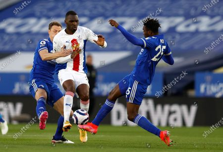 Leicester's Jonny Evans, left, Leicester's Wilfred Ndidi, right, and Crystal Palace's Christian Benteke challenge for the ball during the English Premier League soccer match between Leicester City and Crystal Palace at the King Power Stadium in Leicester, England