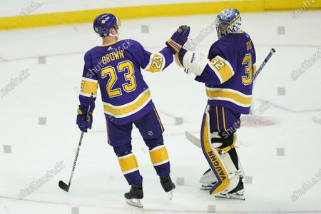 Los Angeles Kings right wing Dustin Brown (23) and goaltender Jonathan Quick (32) high-five after a 4-1 win over the Anaheim Ducks in an NHL hockey game, in Los Angeles