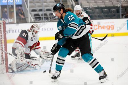 San Jose Sharks defenseman Erik Karlsson (65) takes a shot agains the Arizona Coyotes goaltender Adin Hill (31) during the third period of an NHL hockey game in San Jose, Calif