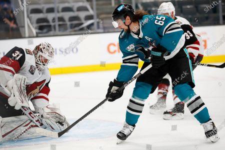 Arizona Coyotes goaltender Adin Hill (31) blocks a shot against the San Jose Sharks defenseman Erik Karlsson (65) during the third period of an NHL hockey game in San Jose, Calif