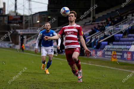 Joe Ward of Peterborough United (23) and Joe Wright of Doncaster Rover (5)