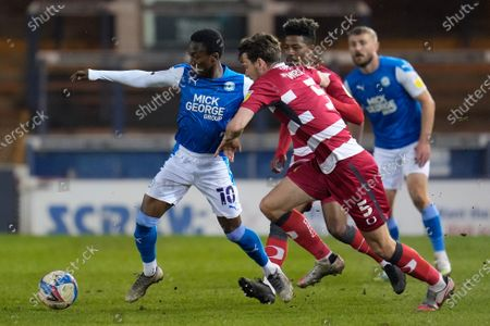 Siriki Dembélé of Peterborough United (10) and Joe Wright of Doncaster Rover (5)