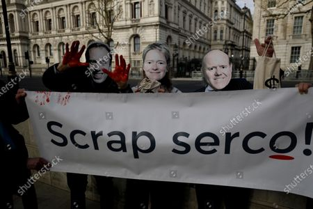 """Supporters of the campaign group """"We Own It"""" pose for photographs wearing masks of, from left, Britain's Health Secretary Matt Hancock, Dido Harding the head of the National Health Service coronavirus Test and Trace programme and Serco CEO Rupert Soames, as they hold an anti-Serco protest banner across the road from the Downing Street entrance gates in London, . The campaigners are calling for the British government not to renew private company Serco's contract for the coronavirus test and trace system, and instead put local public health teams in charge"""
