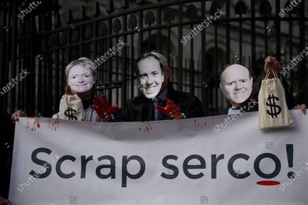 """Supporters of the campaign group """"We Own It"""" pose for photographs wearing masks of, from left, Dido Harding the head of the National Health Service coronavirus Test and Trace programme, Britain's Health Secretary Matt Hancock, and Serco CEO Rupert Soames, as they hold an anti-Serco protest banner outside Downing Street in London, . The campaigners are calling for the British government not to renew private company Serco's contract for the coronavirus test and trace system, and instead put local public health teams in charge"""