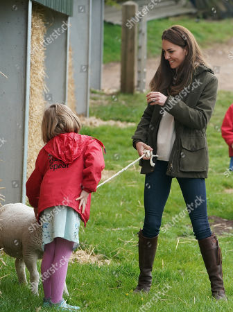 Catherine Duchess of Cambridge and farmer's daughter Clover Chapman, 9, walk a lamb together during a royal visit to Manor Farm in Little Stainton, Durham.