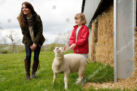 Catherine Duchess of Cambridge is shown a lamb by farmers daughter Clover Chapman 9, during a visit to Manor Farm in Little Stainton, Durham.
