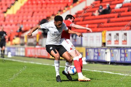 Nathan Thompson of Peterborough battles for possession with Liam Millar of Charlton Athletic during the Sky Bet League 1 match between Charlton Athletic and Peterborough at The Valley, London, England on 24th April 2021.