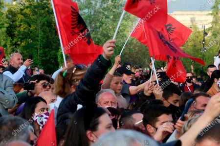 Stock Image of Supporters of Albania's Prime Minister Edi Rama wave flags of their country during a rally in Tirana, Albania, . Albania's left-wing Socialist Party has secured a third consecutive mandate in a parliamentary election, winning a majority of seats in parliament, Prime Minister Edi Rama said on Tuesday